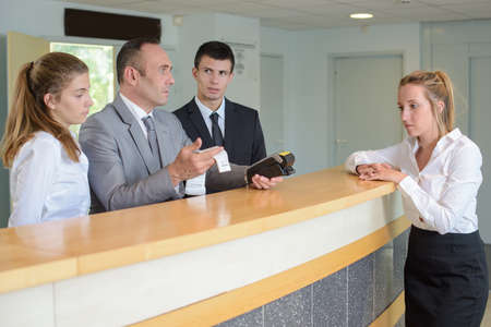 Photo for men behind reception desk looking at computer - Royalty Free Image