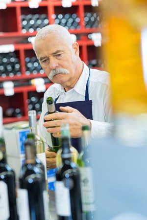 Photo pour senior winemaker working in a wine store - image libre de droit