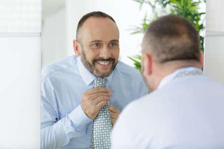 Photo pour handsome man ties up a tie in front of mirror - image libre de droit