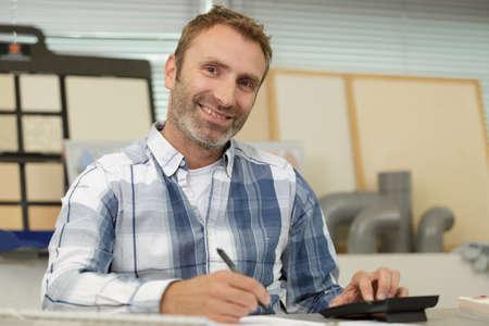 Photo pour happy man showing a calculator - image libre de droit