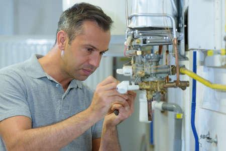 Photo pour male engineer repairing a gas boiler - image libre de droit