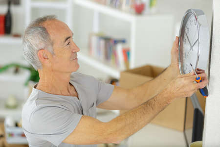 Photo pour fitting a clock on a wall - image libre de droit