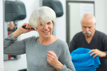 Photo pour senior woman brushing her hair after fitness class - image libre de droit