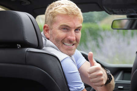 Photo pour male driver turning to back of car with thumbs up - image libre de droit