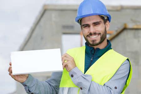 Photo pour happy beard builder in uniform holding an empty white banner - image libre de droit