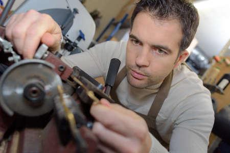 Photo pour Man using bench mounted grinder - image libre de droit