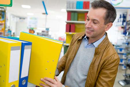 Photo pour man buys folders in a store - image libre de droit