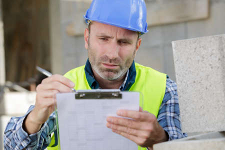 Photo pour male builder or manual worker in helmet writing on clipboard - image libre de droit