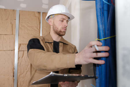 Photo pour technician checking the state of water pipes indoors - image libre de droit