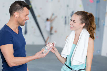 Photo pour handsome man and woman drink water in gym - image libre de droit