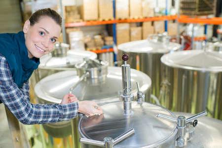 Foto für portrait of woman in brewery stood next to vats - Lizenzfreies Bild