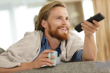 Photo pour happy young man with tv remote control on sofa - image libre de droit