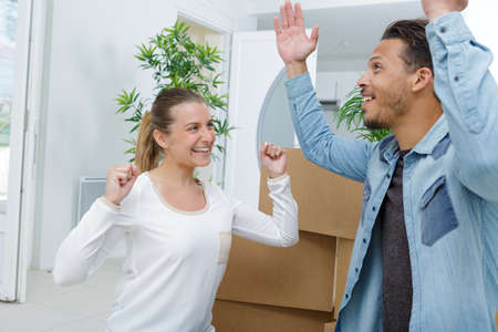 Photo pour happy man and woman jumping among cardboard boxes - image libre de droit