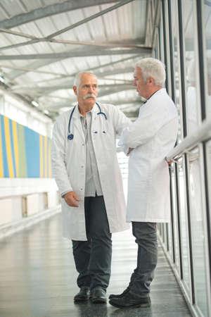 Photo pour two senior doctors talking in the hospital hallway - image libre de droit