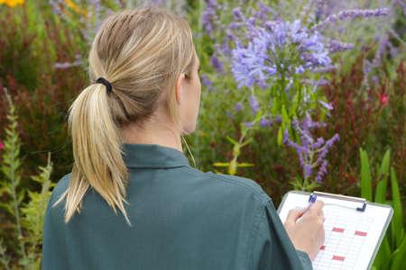 Photo pour female gardener taking notes on the clipboard - image libre de droit