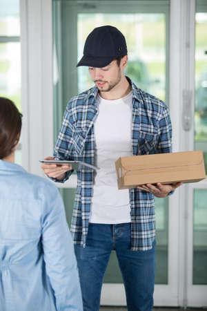 Photo pour young delivery man holding a cardboard - image libre de droit