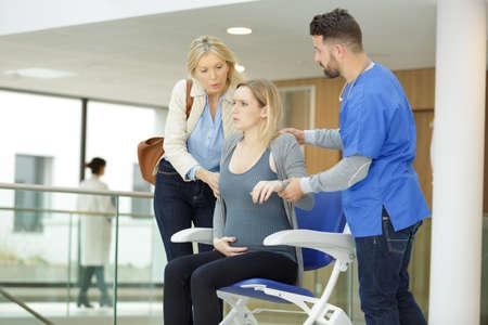 Photo pour a pregnant woman in pain sitting on a wheelchair - image libre de droit