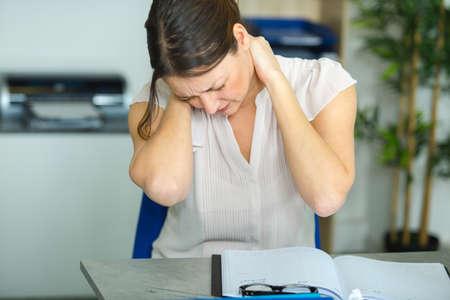 Photo pour female office worker massaging aching neck - image libre de droit