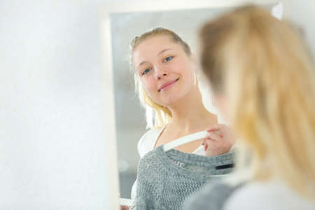 Photo pour beautiful woman trying on clothes in front of the mirror - image libre de droit