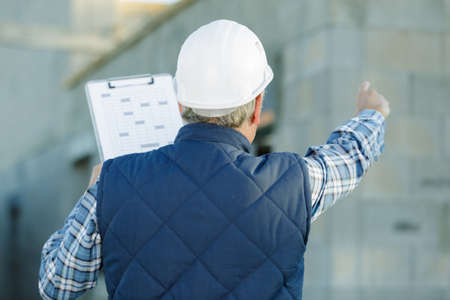 Photo pour engineer holding a clipboard and pointing to something - image libre de droit