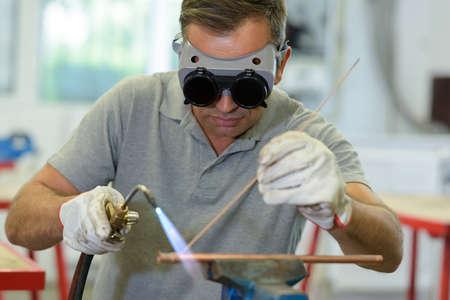 Foto de a worker welding cooper pipes - Imagen libre de derechos