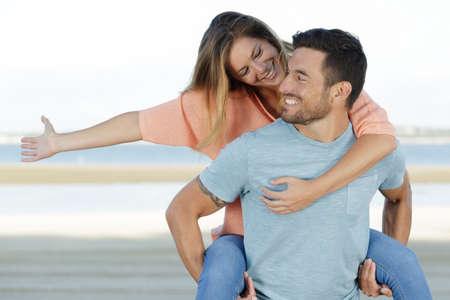 happy man giving woman piggyback on beach