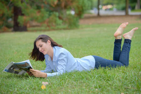Foto per Woman layed on grass reading magazine - Immagine Royalty Free