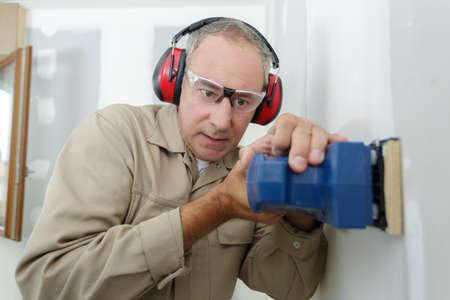 Photo pour Construction worker is sanding a wall - image libre de droit