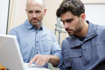Photo pour Portrait of two men holding the laptop - image libre de droit