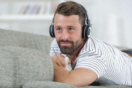 Photo pour smiling man listening to music with headphones - image libre de droit