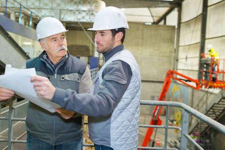 Photo pour Builder with blueprint shaking partner hand - image libre de droit