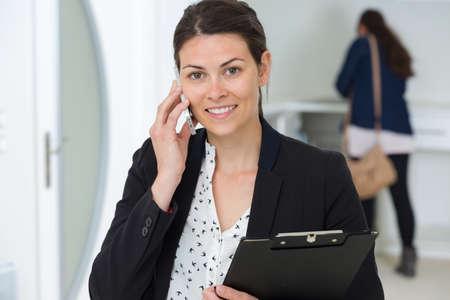Photo pour young business woman with a clipboard indoors - image libre de droit