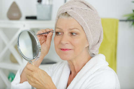 Photo pour Senior woman plucking her eyebrows with tweezers - image libre de droit