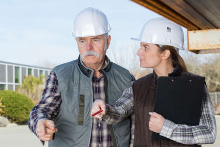 Photo pour two architects mature man and young woman working on site - image libre de droit