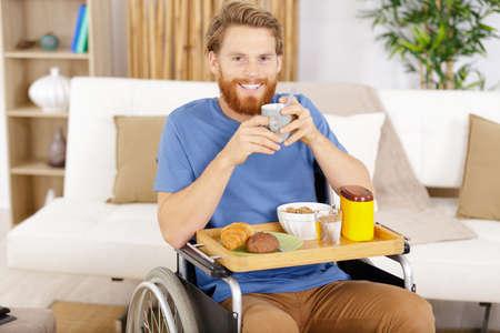 Photo pour a man in wheelchair user having breakfast - image libre de droit