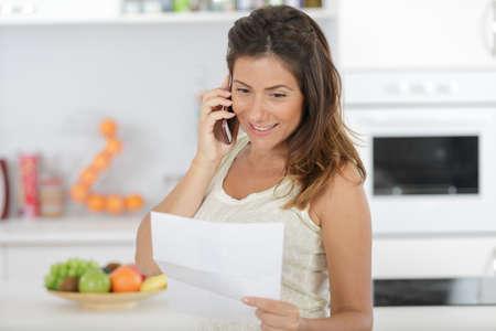 Photo pour young smiling businesswoman talking by phone - image libre de droit