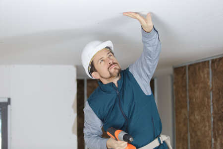 Foto de house renovation worker checking the alignment of a ceiling - Imagen libre de derechos