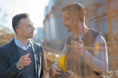 Photo pour manual worker talking to manager by rebars - image libre de droit