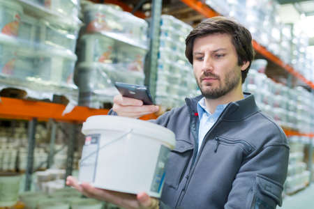 Photo pour storeman scanning product in plastic container with smartphone - image libre de droit
