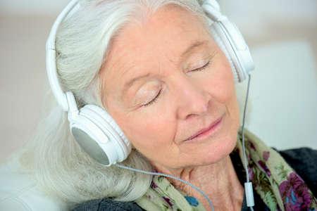 Photo pour a senior woman in headphones - image libre de droit