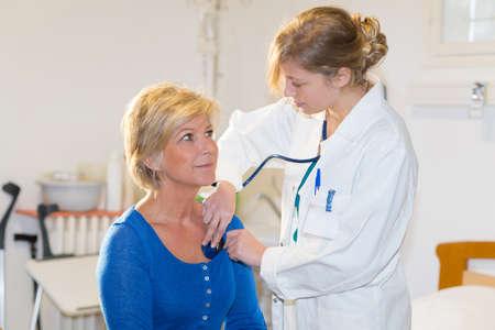 Photo pour female doctor checking blood pressure of senior woman - image libre de droit