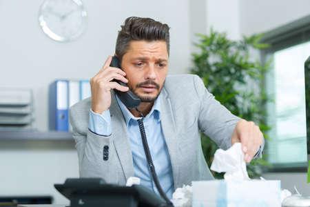 Photo pour businessman on the telephone reaching for a tissue - image libre de droit