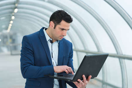 Photo pour businessman using portable laptop in arched walkway - image libre de droit