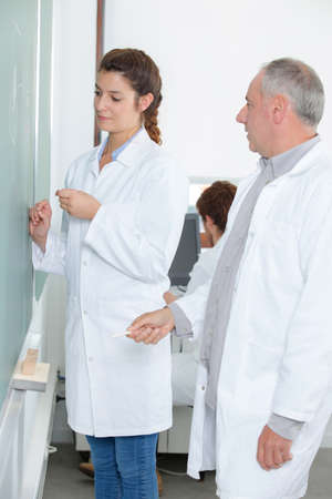 Photo pour Young female student write chemical formula on blackboard - image libre de droit