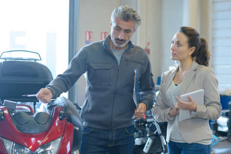 Photo for woman motrbike store seller discussing with male customer - Royalty Free Image
