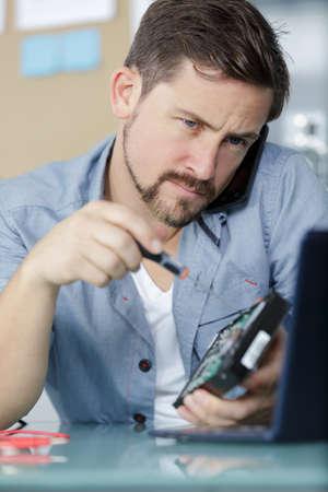 Photo pour young technician working on broken computer - image libre de droit