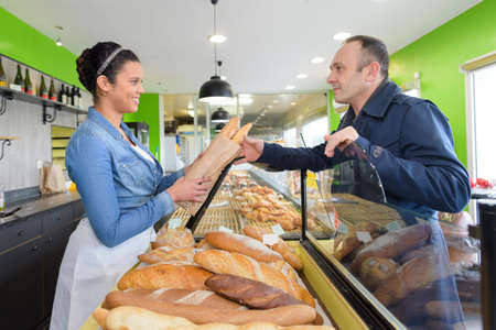 Photo pour woman serving bread to male customer in bakery - image libre de droit
