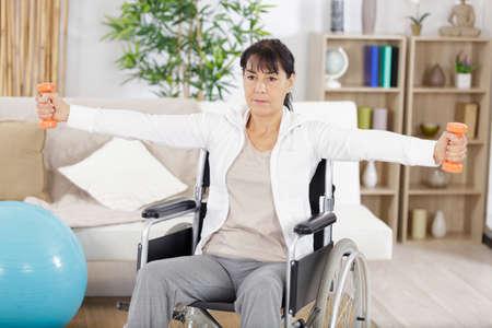 Photo pour woman on wheelchair holding weights - image libre de droit