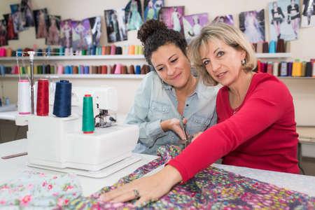 Photo pour mom teaches daughter how to sew - image libre de droit