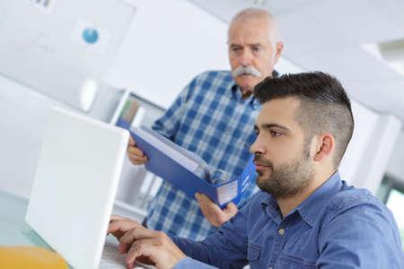 Photo pour grandson teaching grandfather how to use laptop - image libre de droit